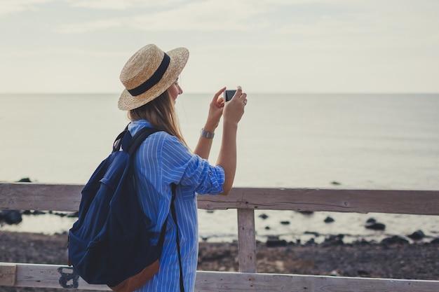 Viaggiatore della donna che cammina sulla spiaggia di vlychada in akrotiri sull'isola di santorini, in grecia. foto di presa turistica del mare Foto Premium