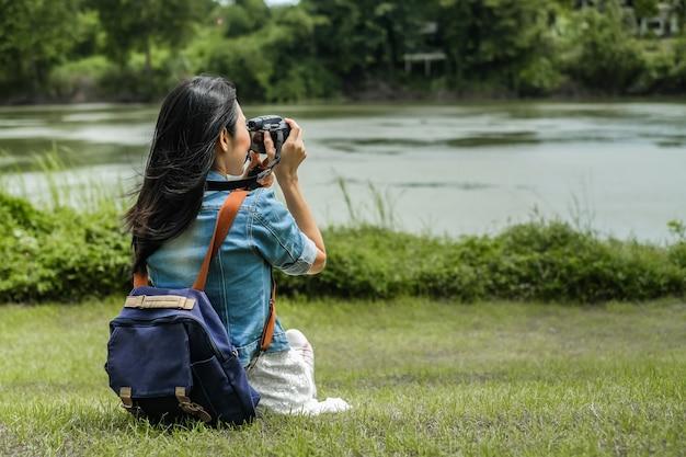 Viaggiatore della donna che si siede sull'erba e che prende la vista della foto della diga Foto Premium