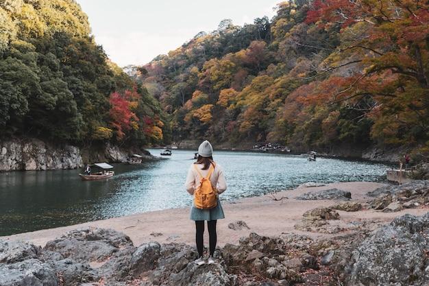 Viaggiatore della giovane donna che guarda bello paesaggio a arashiyama giappone, stile di vita di viaggio Foto Premium