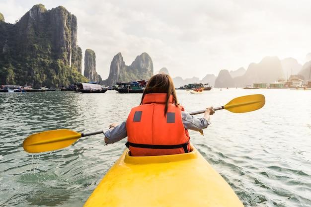 Viaggiatore della giovane donna che rema il kajak nella baia tropicale Foto Premium