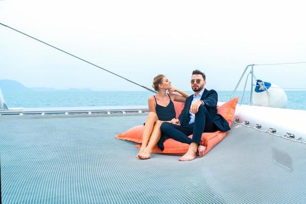 Viaggiatore di coppia rilassante di lusso in bel vestito e suite sedersi sulla borsa di fagioli in parte dello yacht da crociera. Foto Premium