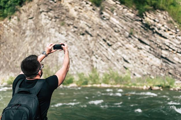 Viaggiatore di yong che prende foto vicino al fiume della montagna Foto Premium