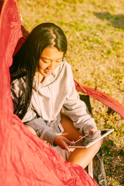 Viaggiatore femminile con tavoletta seduto in tenda Foto Gratuite