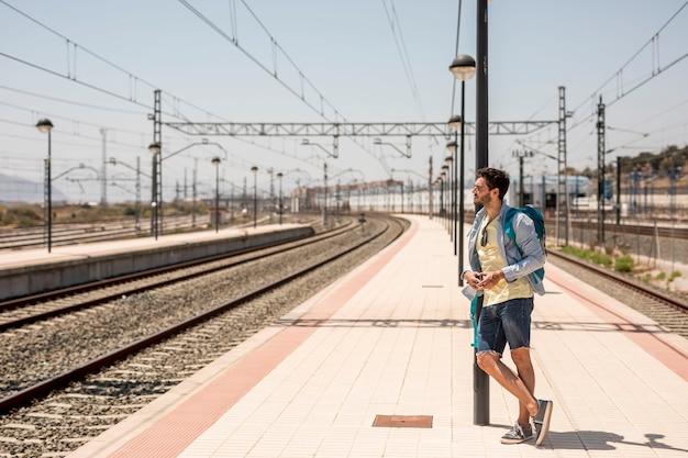 Viaggiatore laterale appoggiato al palo Foto Gratuite