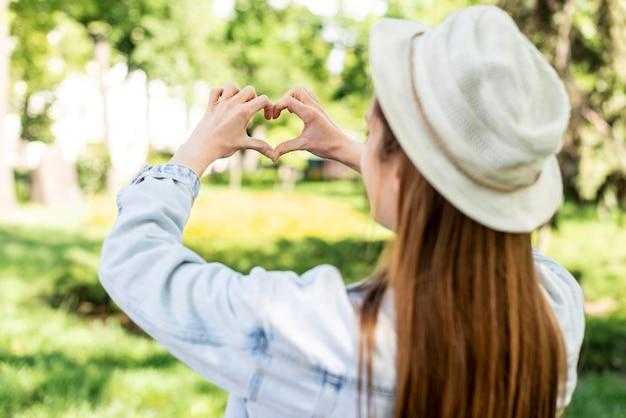 Viaggiatore nel parco che fa una forma di cuore da dietro il colpo Foto Gratuite