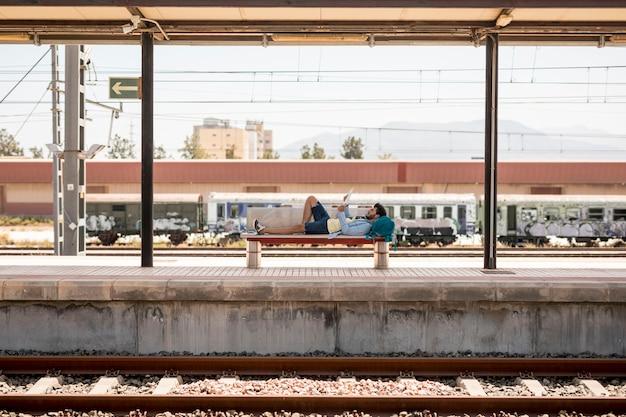 Viaggiatore sdraiato sulla panchina in attesa del treno Foto Gratuite