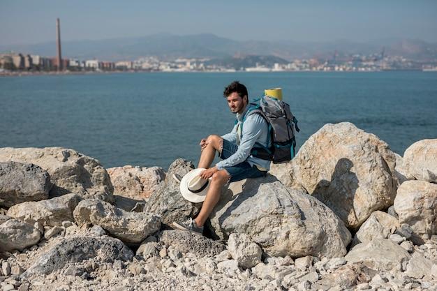 Viaggiatore seduto sulle rocce in riva al mare Foto Gratuite