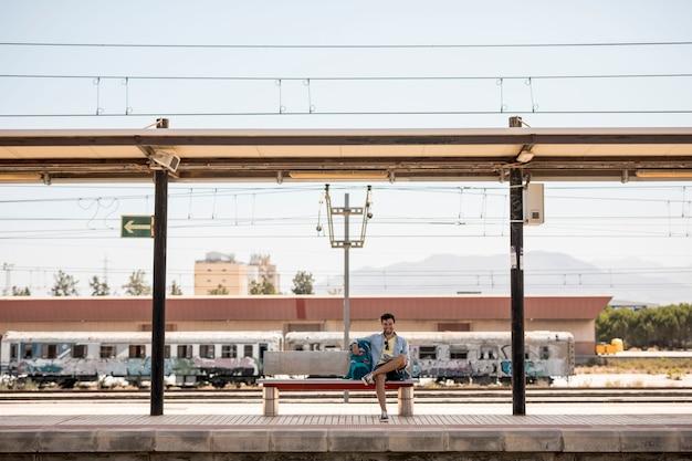 Viaggiatore sorridente del colpo lungo che aspetta treno Foto Gratuite
