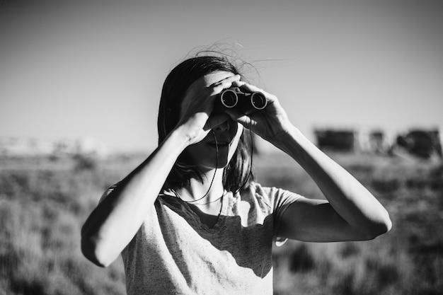 Viaggiatore usando un binocolo per individuare un uccello Foto Gratuite