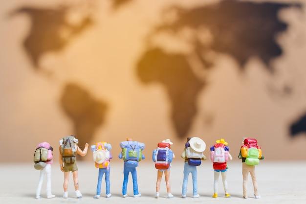 Viaggiatori di persone in miniatura che camminano sulla mappa del mondo Foto Premium