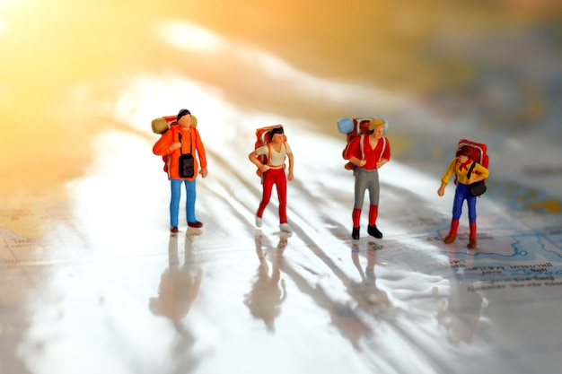 Viaggiatori in miniatura con zaino in piedi sulla mappa, viaggi e concetto di avventura. Foto Premium