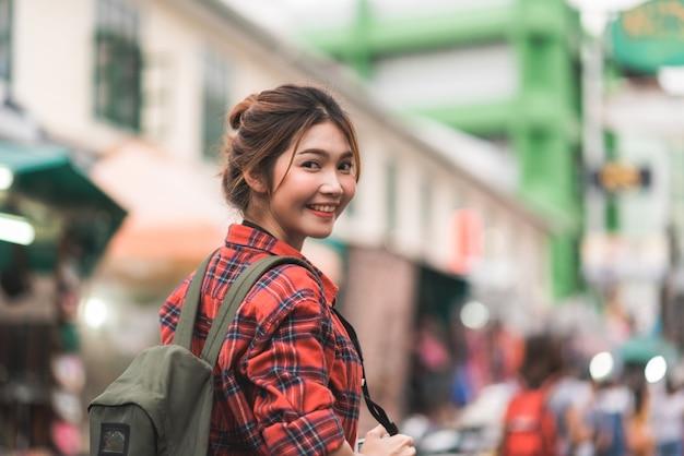 Viaggio asiatico della donna di viaggiatore con zaino e sacco a pelo del viaggiatore in strada di khao san a bangkok, tailandia Foto Gratuite