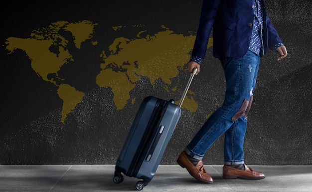 Viaggio . giovane con bagagli a piedi dal muro. mappa del mondo Foto Premium