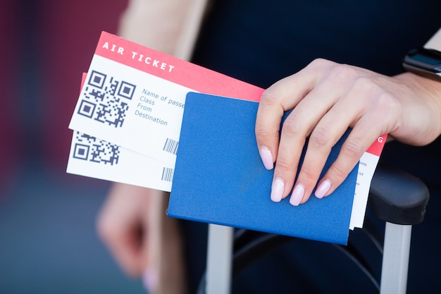 Viaggio. primo piano dei passaporti della holding della ragazza e della carta d'imbarco all'aeroporto Foto Premium