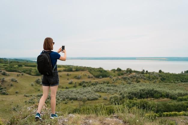 Viandante della donna che prende foto con lo smart phone al picco della collina. Foto Gratuite