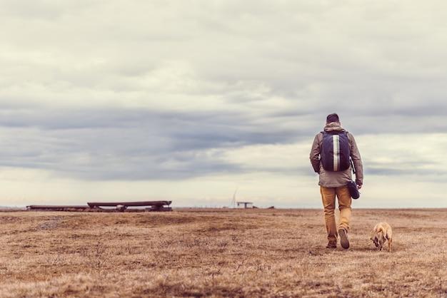 Viandante e cane che camminano nel pascolo Foto Premium