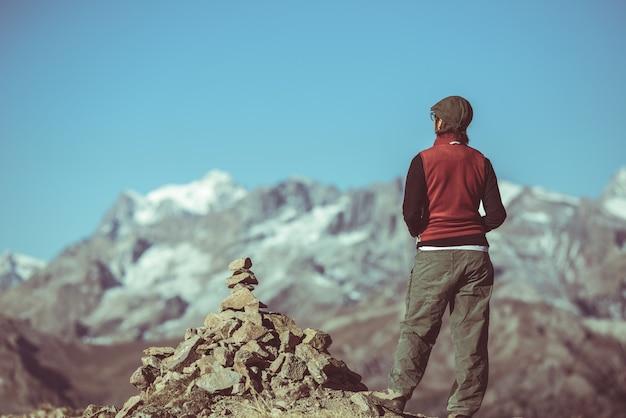 Viandante sulla cima della montagna che esamina vista panoramica, parco nazionale del massiccio degli ecrins, le alpi Foto Premium