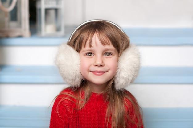 Vicino ritratto di una bambina carina in un maglione rosso seduto sul portico di casa in inverno. bambino sorridente si siede su una scala in legno in strada. il bambino gioca nel cortile invernale vicino a casa. vigilia di natale Foto Premium