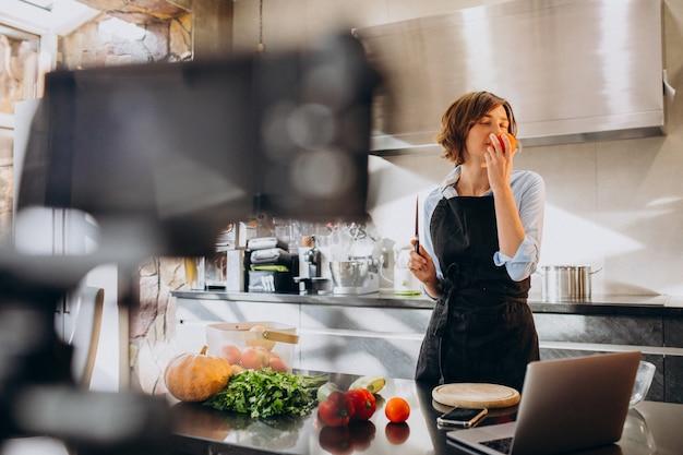 Videoblogger della giovane donna che cucina alla cucina e alle riprese Foto Gratuite