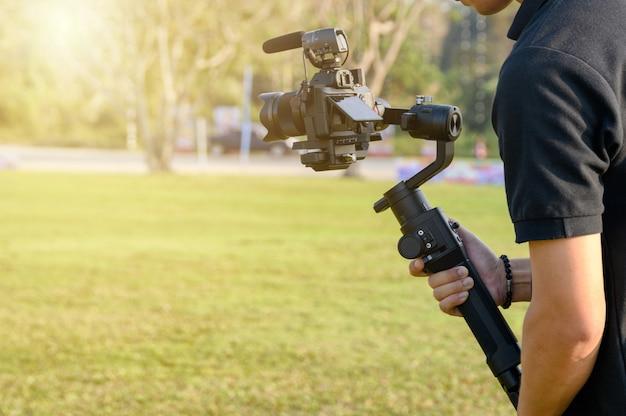 Videografo professionista con fotocamera su stabilizzatore cardanico per l'assunzione Foto Premium