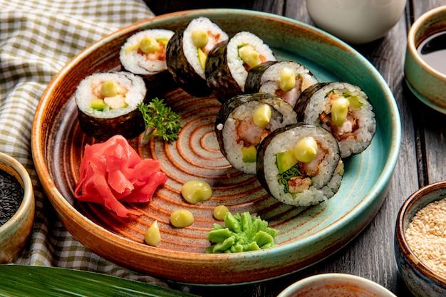 Vie laterali di involtini di sushi con gamberi tempura di avocado e crema di formaggio su un piatto con zenzero e wasabi Foto Gratuite
