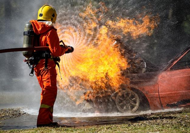 Vigile del fuoco che hosing l'acqua per estinguere un fuoco sopra l'automobile nell'incidente Foto Premium