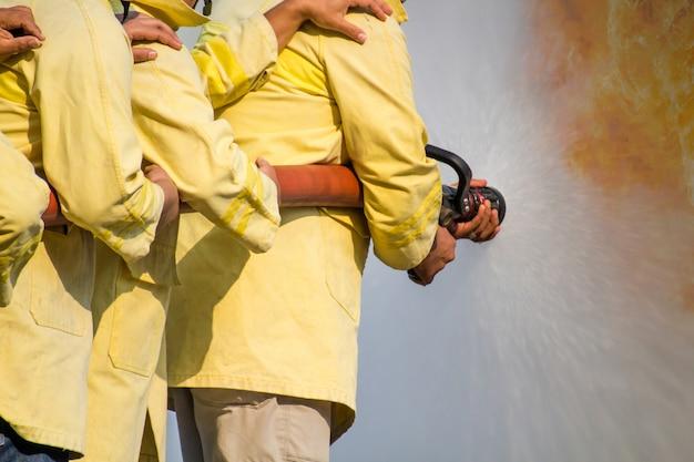 Vigili del fuoco che utilizzano acqua dal tubo per antincendio all'addestramento di lotta antincendio del gruppo assicurativo. pompiere che indossa una tuta antincendio per sicurezza sotto il caso di addestramento al pericolo. Foto Premium