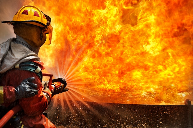 Vigili del fuoco usando l'estintore e l'acqua dal tubo per la lotta antincendio all'allenamento a fuoco Foto Premium