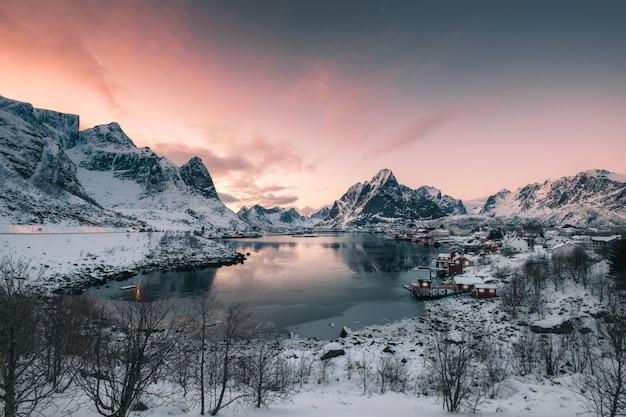 Villaggio di pescatori in montagna di neve con il cielo al tramonto a costa Foto Premium