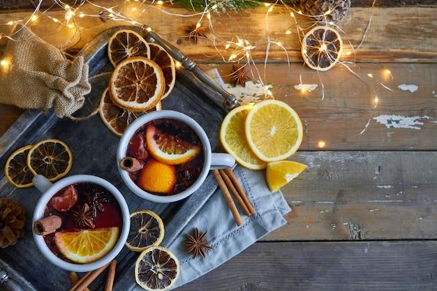 Vin brulè di natale in due tazze rustiche con frutta e spezie sul tavolo di legno Foto Premium
