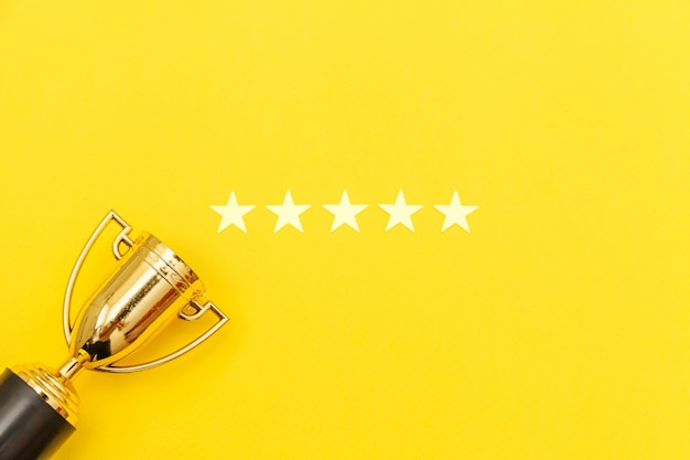 Vincitore del design semplicemente piatto o campione coppa d'oro trofeo e 5 stelle valutazione isolato su sfondo rosa pastello. vittoria primo posto di competizione. concetto vincente o di successo. vista dall'alto copia spazio. Foto Premium
