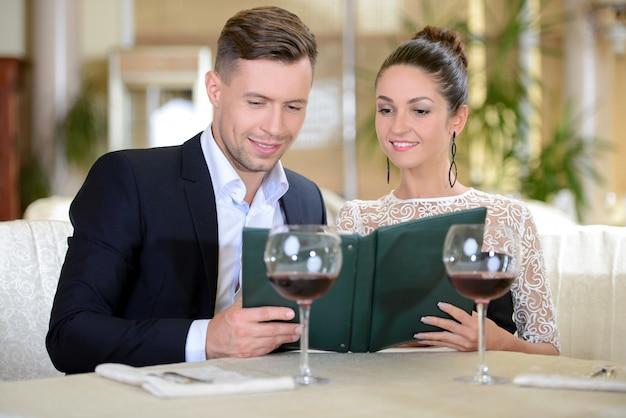 Vino bevente delle coppie eleganti che si siede nel buon ristorante Foto Premium