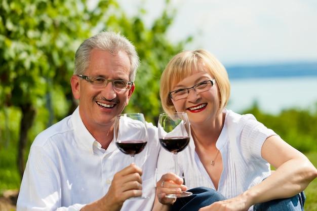 Vino bevente delle coppie senior felici all'aperto Foto Premium