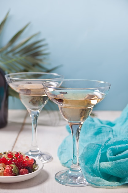Vino bianco in bicchieri, bottiglia e piatto con frutti di bosco. Foto Premium