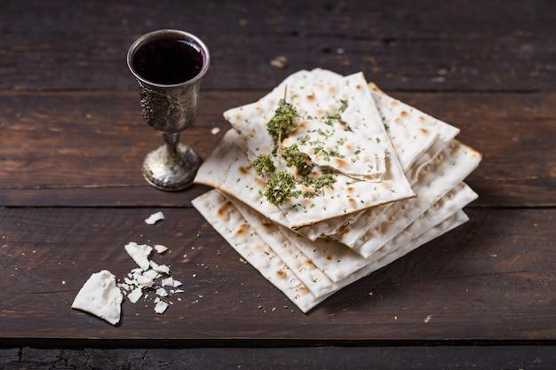 Vino kosher rosso con un bianco matzah o matza su una parete di legno vintage presentato come un pasto seder pasquale con spazio di copia. Foto Premium