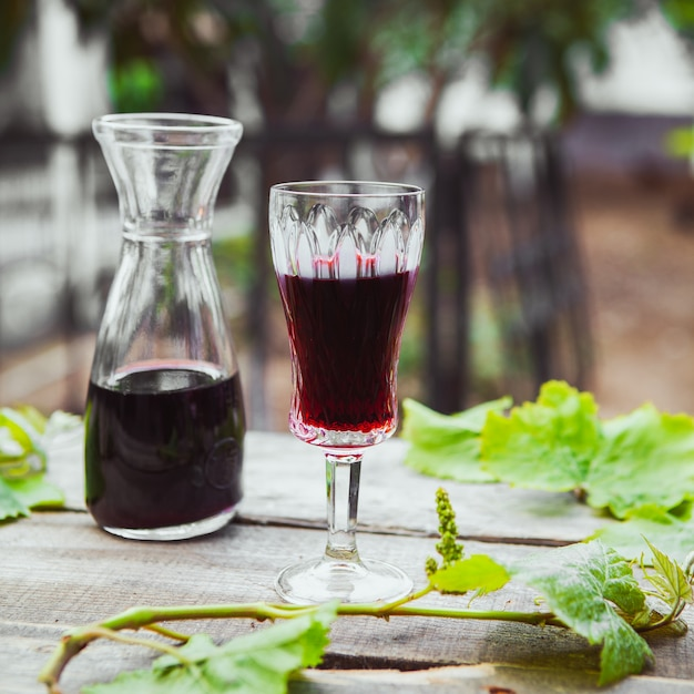 Vino rosso in brocca e vetro con la vista laterale del ramo di uva sulla tavola di legno e del giardino Foto Gratuite