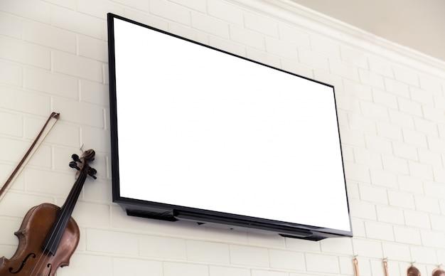 Violino accanto ad uno schermo televisivo in bianco Foto Gratuite