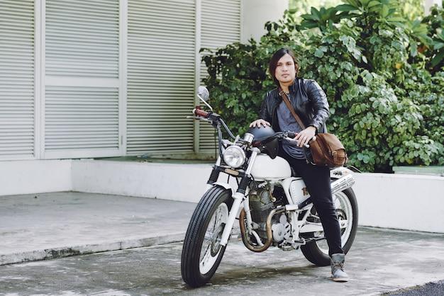 Vista a figura intera del motociclista pronto a guidare la sua moto Foto Gratuite