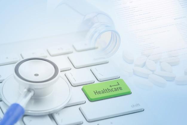 Vista a macroistruzione di uno stetoscopio sulla tastiera di computer e sul tasto botton con assistenza sanitaria con la pillola Foto Premium