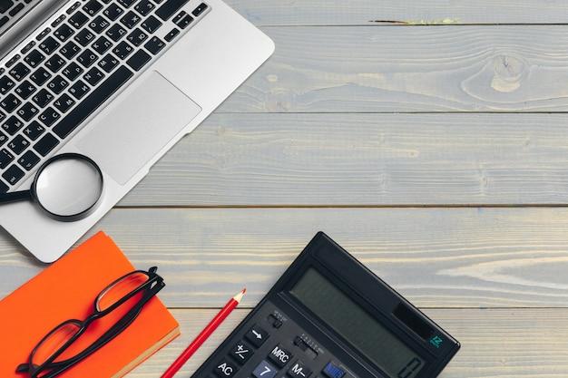 Vista ad angolo della tastiera e dei vetri del computer portatile con i vari articoli per ufficio sullo scrittorio di legno Foto Premium
