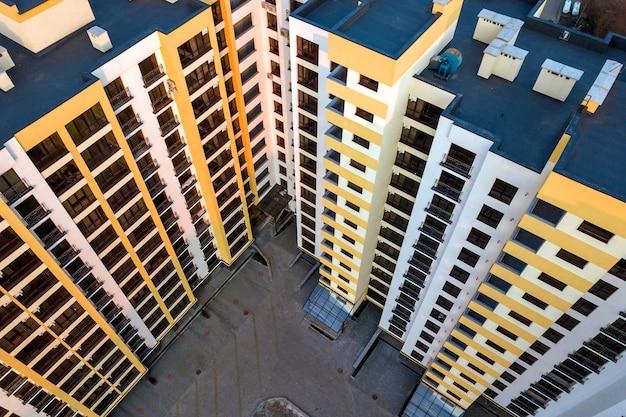 Vista aerea del complesso di condominio alto. tetto piano blu con camini, cortile interno, fila di finestre. fotografia di droni. Foto Premium