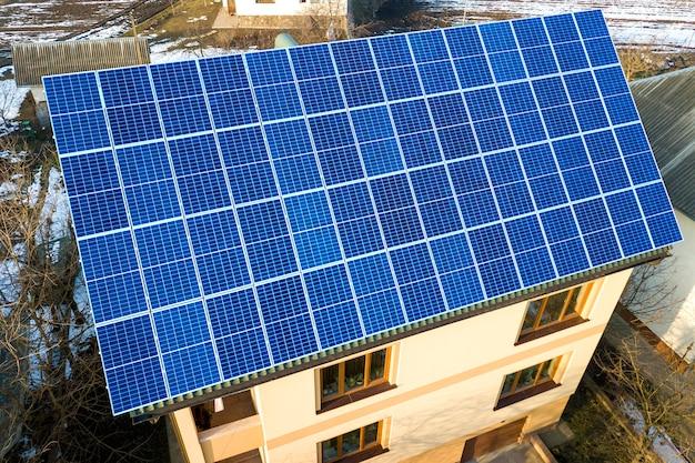 Vista aerea del nuovo moderno cottage a due piani con sistema fotovoltaico solare lucido blu sul tetto. concetto di produzione di energia verde ecologica rinnovabile. Foto Premium