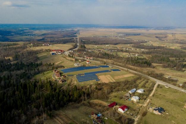 Vista aerea del sistema fotovoltaico blu blu dei pannelli fotovoltaici che produce energia pulita rinnovabile su paesaggio rurale Foto Premium