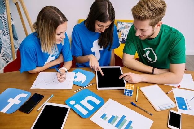 Vista aerea del team di rete di media sociali guardando la tavoletta digitale Foto Gratuite