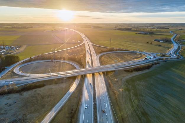 Vista aerea dell'intersezione moderna della strada della strada principale all'alba su paesaggio rurale e sollevare il fondo del sole. fotografia di droni. Foto Premium