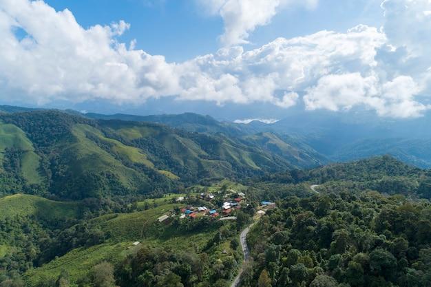 Vista aerea della curva della strada sulla foresta pluviale tropicale di montagna, vista a volo d'uccello immagine sopra le nuvole incredibile paesaggio naturale con nuvole e picchi di montagna Foto Premium