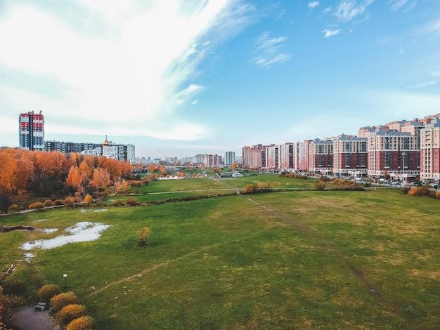 Vista aerea della periferia, bellissimo parco autunnale e grattacielo residenziale. san pietroburgo, russia Foto Premium