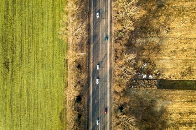 Vista aerea della strada diritta con auto in movimento, alberi e campi verdi in giornata di sole. fotografia di droni. Foto Premium