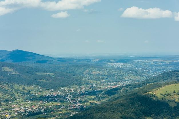 Vista aerea della valle di montagna verde con la città Foto Gratuite