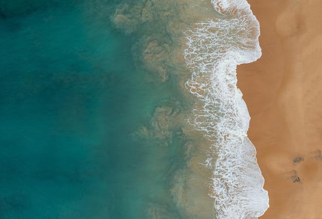 Vista aerea delle belle onde dell'oceano che incontrano le sabbie sulla spiaggia Foto Gratuite